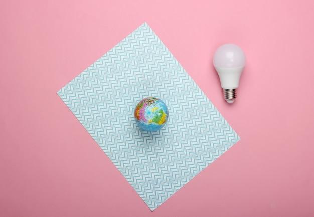 Rette den planeten. öko-konzept. energiesparende led-glühbirne und globus auf rosa-blauem pastellhintergrund