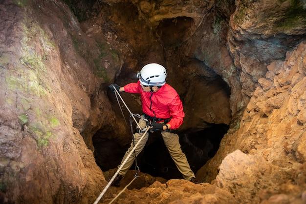 Retter oder kletterer steigen in einem höhlenschnellen seil in den dunklen höhlen ab