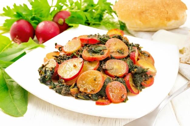 Rettich gedünstet mit spinat und gewürzen in einem teller, käse und brot, serviette vor holzbrett hintergrund