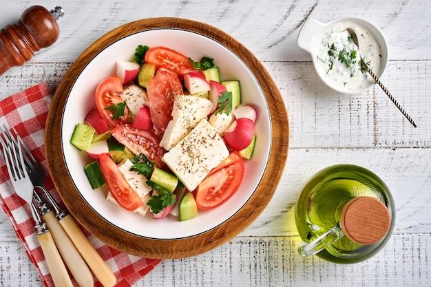 Rettich, gurke, tomate, pfeffer und feta-käse mit gewürzpfeffer und olivenöl in weißer schüssel auf grauem schiefer-, stein- oder betonhintergrund. gesundes lebensmittelkonzept. ansicht von oben.