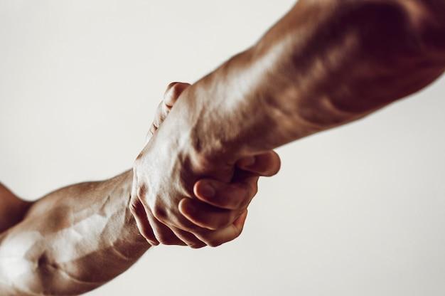 Rettung, helfende geste oder hände. starker halt. zwei hände, helfende hand eines freundes. händedruck, arme, freundschaft. freundlicher händedruck, freunde grüßen, teamwork, freundschaft. nahaufnahme.