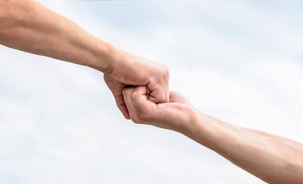 Rettung, helfende geste oder hände. zwei hände, helfender arm eines freundes, teamwork. helfende hand ausgestreckt. freundlicher händedruck, begrüßung durch freunde