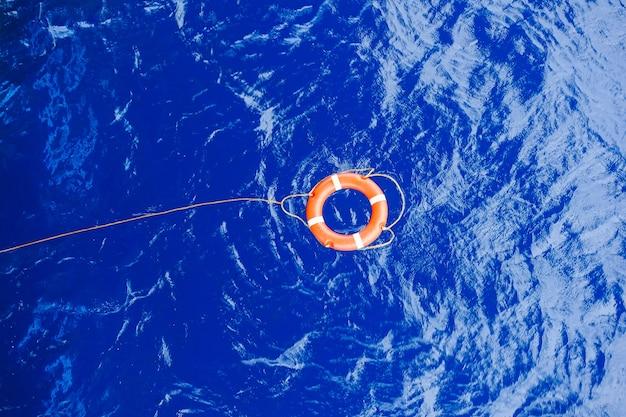 Rettungsboje gebunden mit der seilrettung, die in das meer schwimmt.