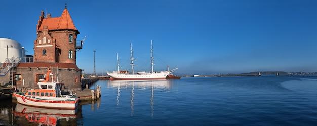 Rettungsboot vor historischem backsteinbau in hafeninsel und historischem segelschiff in stralsund