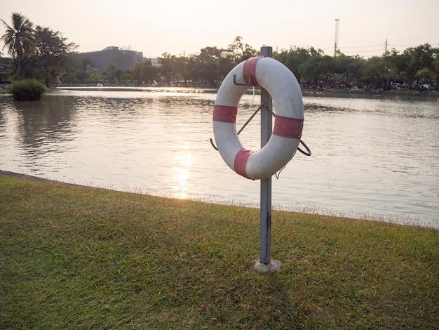 Rettungsring, erhalter auf pole im park bei sonnenuntergang