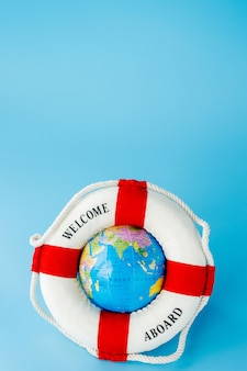 Rettungsring und globus auf blauem hintergrund