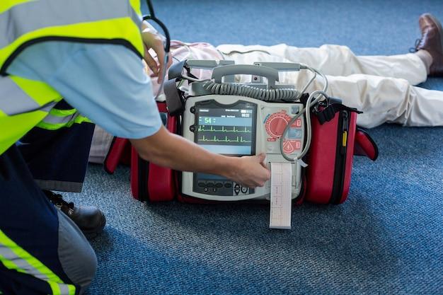 Rettungssanitäter, der einen externen defibrillator während der kardiopulmonalen wiederbelebung verwendet