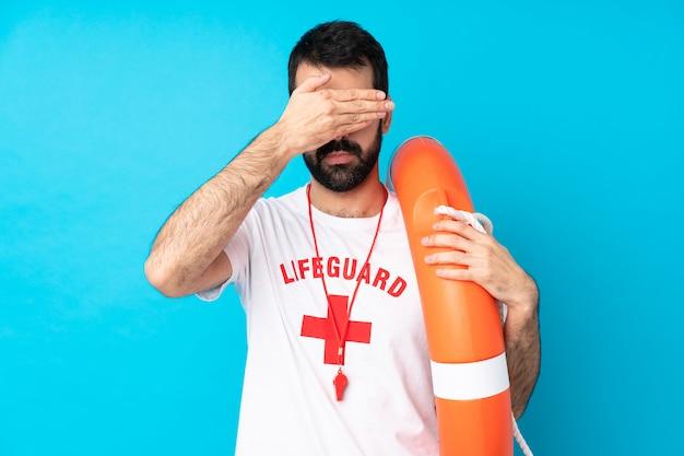 Rettungsschwimmer mann, der augen mit den händen bedeckt. ich will nichts sehen