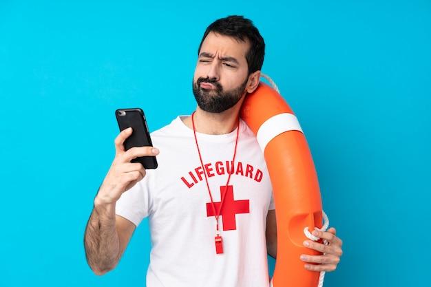 Rettungsschwimmer mann über isolierte blaue wand denken und eine nachricht senden