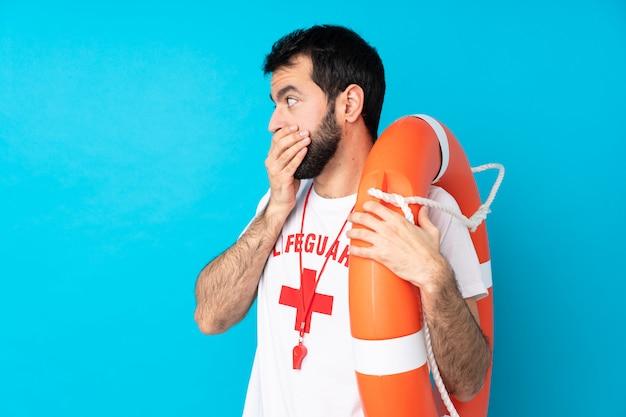 Rettungsschwimmer mann über isolierte blaue wand, die mund bedeckt und zur seite schaut