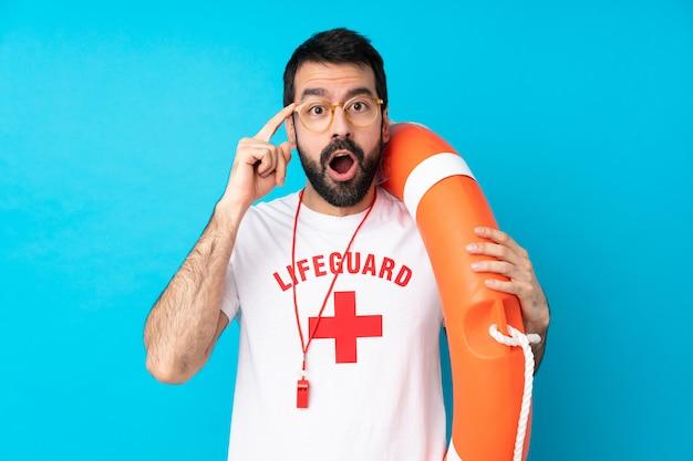 Rettungsschwimmer mann über isolierte blaue wand mit brille und überrascht