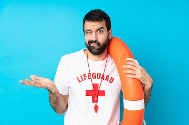 Rettungsschwimmer mann über isolierte blaue wand unglücklich, etwas nicht zu verstehen