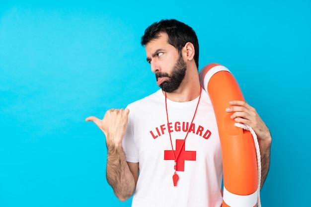 Rettungsschwimmer mann über isolierte blaue wand unglücklich und zur seite zeigend