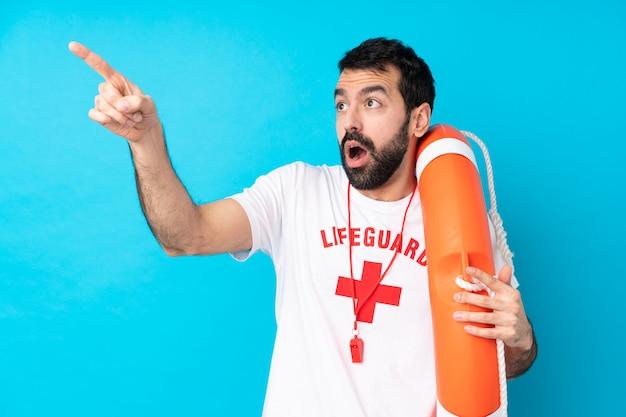 Rettungsschwimmer mann über isolierte blaue wand zeigt weg