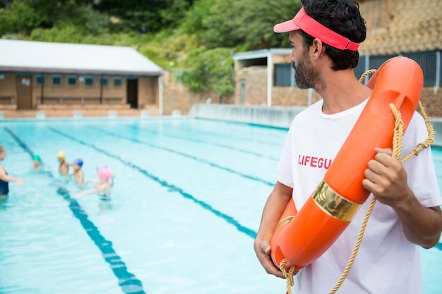 Rettungsschwimmer mit rettungsring, der studenten betrachtet, die an einem sonnigen tag im pool spielen