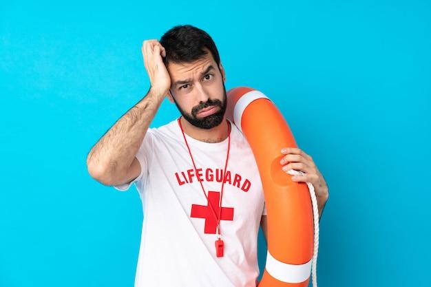 Rettungsschwimmer über isolierte blaue wand mit einem ausdruck der frustration und des unverständnisses