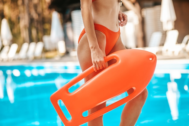 Rettungsschwimmer. weiblicher rettungsschwimmer in einem roten badeanzug, der in der nähe des öffentlichen schwimmbads steht