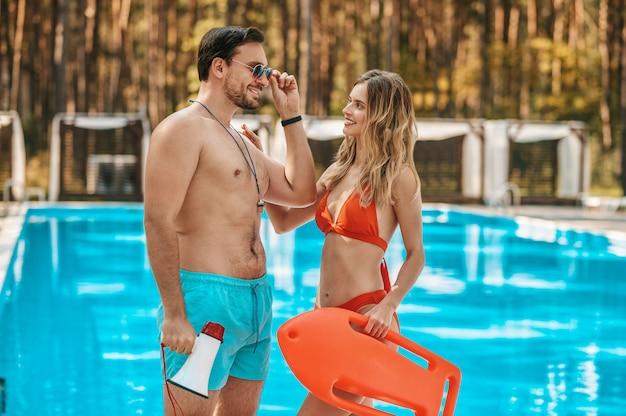 Rettungsschwimmer. zwei bademeister stehen in der nähe des öffentlichen schwimmbads