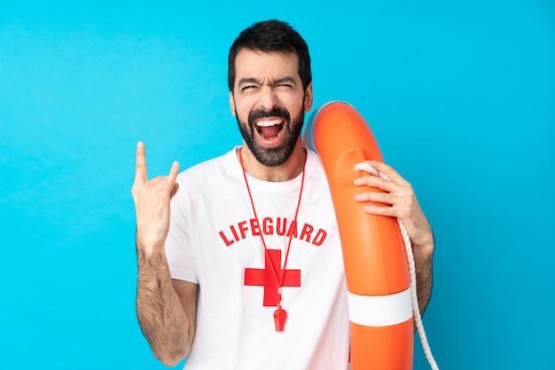Rettungsschwimmermann über blau, der felsengeste macht