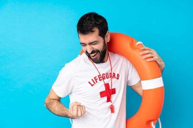 Rettungsschwimmermann über isolierter blauer wand, die einen sieg feiert