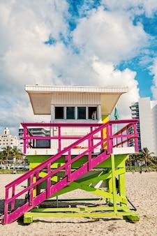Rettungsschwimmerturm, bunte holzstation, auf sand, sandstrand, tropisches palmenresort, an einem sonnigen tag auf der skyline der stadt mit weißen wolken am blauen himmel. idyllischer sommerurlaub. sicherheit. überwachung