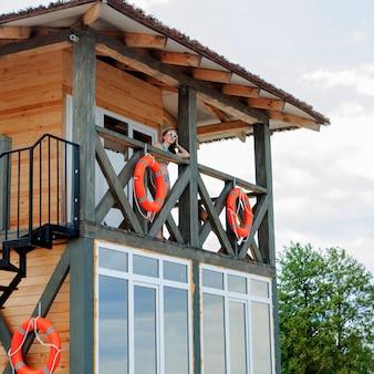 Rettungsschwimmerturm für die rettung baywatch am strand. holzhaus am seeufer am bewölkten himmel. sommerferien und resort. konzept der öffentlichen bewachung und sicherheit