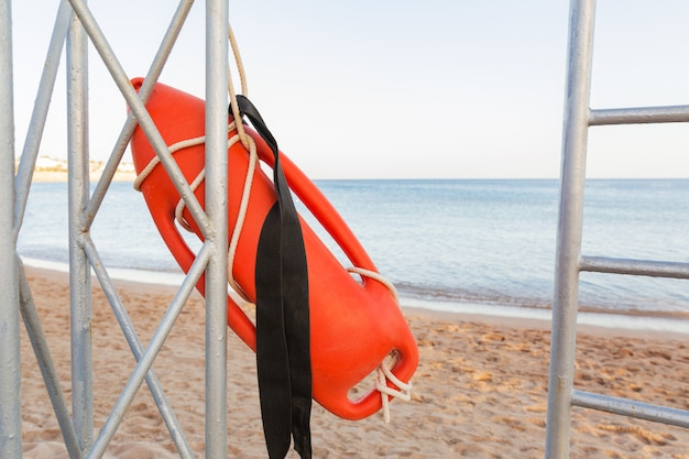 Rettungsschwimmerturm mit orangefarbener boje am strand. rettungsboje auf dem eisernen rettungsposten