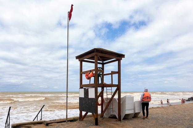 Rettungsturm und rettungsschwimmer in einer orangefarbenen weste am ufer während eines sturms leerer strand am ende der ferienzeit