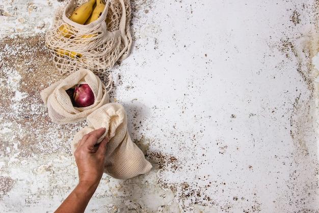 Reutilizable einkaufstasche mit bananen- und gemüsestofftaschen mit kartoffeln und zwiebeln in einer tabelle und jemand, der eine jener taschen nimmt