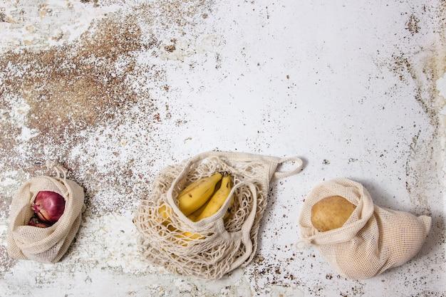 Reutilizable einkaufstasche mit bananen- und gemüsestofftaschen mit kartoffeln und zwiebeln in einer tabelle