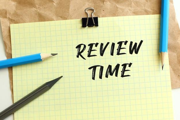 Review time-schriftzug auf einem gelben blatt papier über zerknittertem kraftpapier