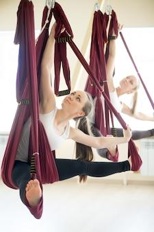 Revved sitzender winkel yoga pose in hängematte