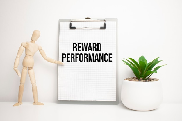 Reward performance-schild auf kleinem holzbrett auf der staffelei mit medizinischem stethoskop