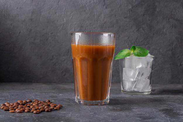 Rezept eiskaffee mit minze und milch. großes glas kaffeecocktail und glas mit eiswürfeln. kühles sommergetränk auf dunklem hintergrund im gesetzesschlüssel. platz für text kopieren