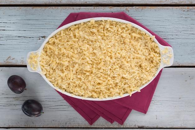 Rezept für bio-pflaumenkuchen, produkte auf dem rustikalen tisch.