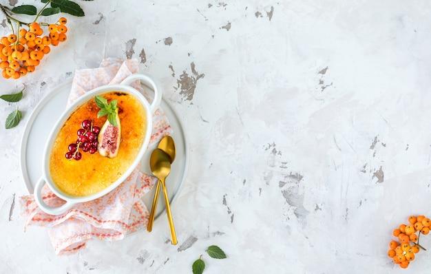 Rezept für creme brulee dessert mit frischen feigen und johannisbeeren auf einem weißen teller in einer herbstkomposition, kopierraum. ansicht von oben