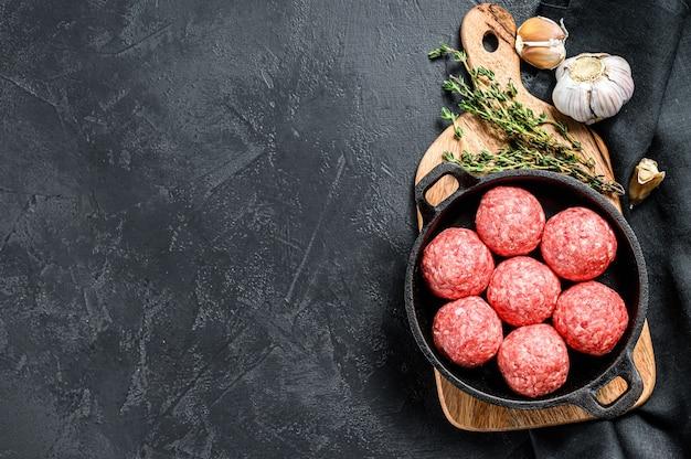 Rezept zum kochen von fleischbällchen aus rinderhackfleisch in einer pfanne. schwarzer hintergrund. draufsicht. speicherplatz kopieren