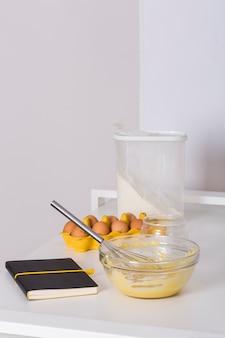 Rezeptbuch; eierkarton; mehl und geschlagene eier auf weißem tisch gegen weiße wand