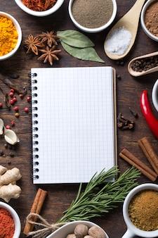 Rezeptbuch mit frischen kräutern und gewürzen öffnen
