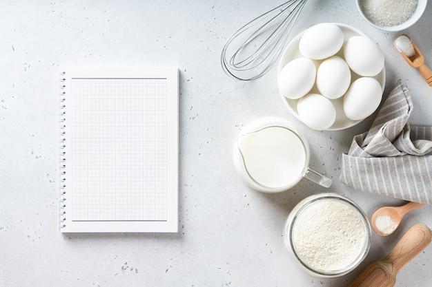 Rezeptbuch und backzutaten auf einer weißen tischansicht von oben