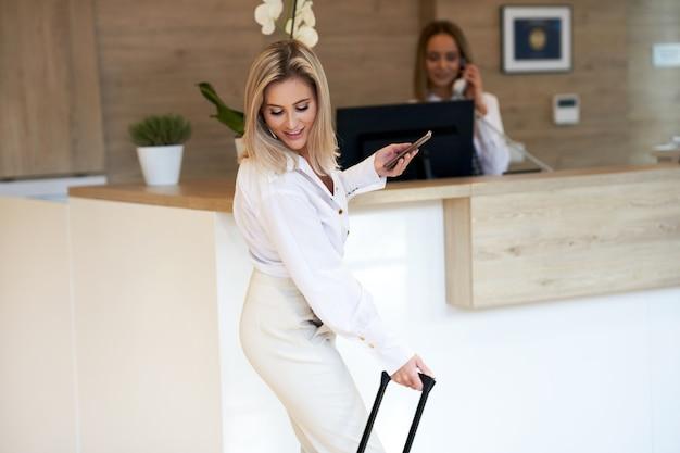 Rezeptionistin und geschäftsfrau an der hotelrezeption