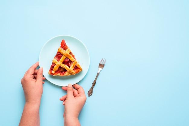 Rhabarber-erdbeer-kuchenscheibe. frau hände, die stück kuchen dienen