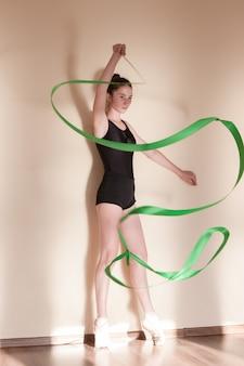 Rhythmische gymnastik. anmutige ballerina in bewegung. jugendsport, gesunder jugendlicher lebensstil. selbstbewusstes mädchen mit grünem band, tanzkurshintergrund, übungskonzept