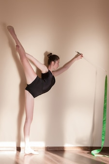 Rhythmische gymnastik. anmutige mädchenflexibilität. jugendsport, gesunder jugendlicher lebensstil. schöne ballerina mit grünem band, brauner hintergrund mit freiem platz, übungskonzept