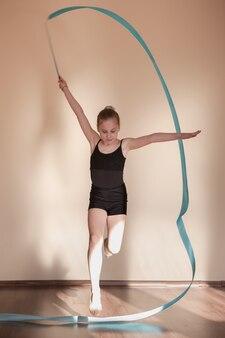 Rhythmische gymnastik. anmutiges mädchen in bewegung. jugendsport, gesunder jugendlicher lebensstil. aufmerksame ballerina mit blauem band, brauner hintergrund mit freiraum, übungskonzept