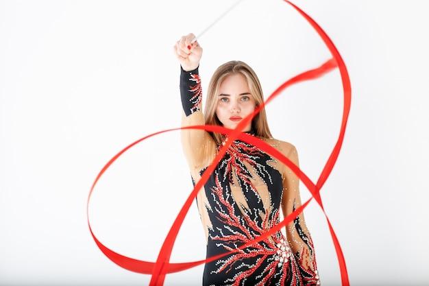 Rhythmische gymnastik. junges turnermädchen mit rotem band auf weiß