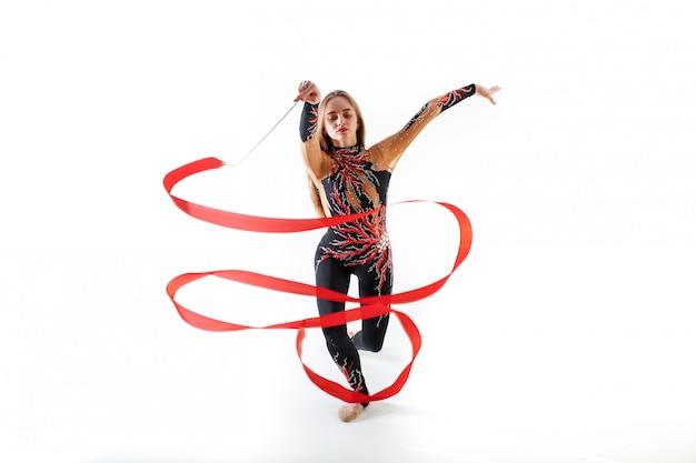 Rhythmische gymnastik. junges turnermädchen mit rotem band auf weißem hintergrund