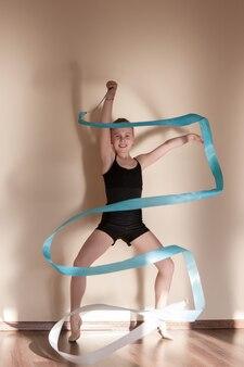 Rhythmische gymnastik. starke selbstbewusste ballerina. jugendsport, gesunder jugendlicher lebensstil. junges mädchen mit blauem band in bewegung, brauner hintergrund mit freiem raum, ballettkonzept