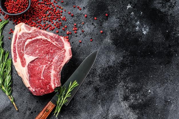 Ribeye am knochen oder cowboy-steak. rohes marmorrindfleisch. schwarzer hintergrund. draufsicht. speicherplatz kopieren.