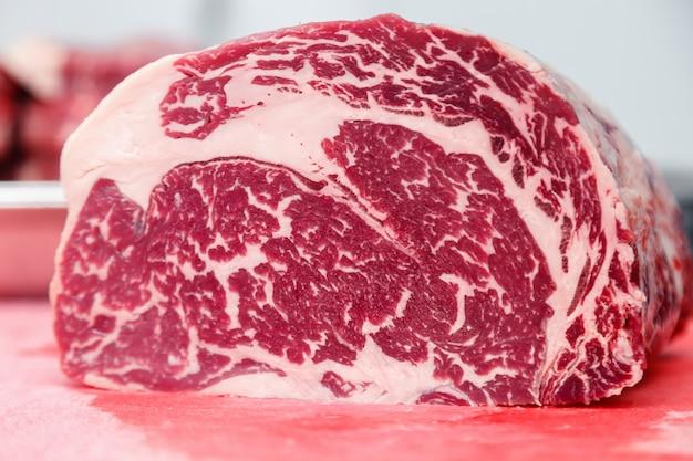 Ribeye gemarmortes rindfleischsteak der nahaufnahmemakrostücke auf rotem plastikschneidebrett.